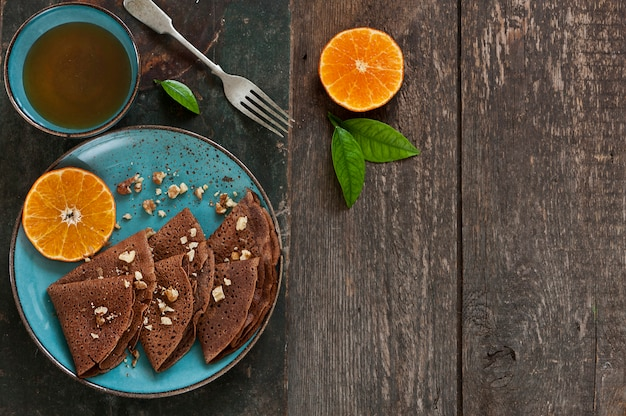 Chocolate pancakes with oranges on blue plate with cup of tea on wooden table Premium Photo