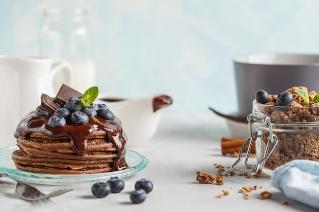 Chocolate pancakes with syrup and berries, chocolate granola and milk. breakfast concept, blue background Premium Photo