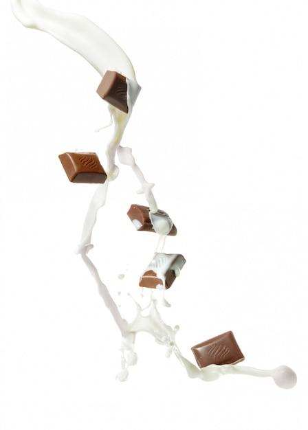 Кусочки шоколада и брызги молока Premium Фотографии