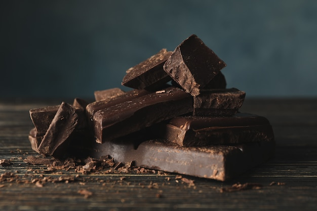Chocolate pieces on wooden background, close up Premium Photo