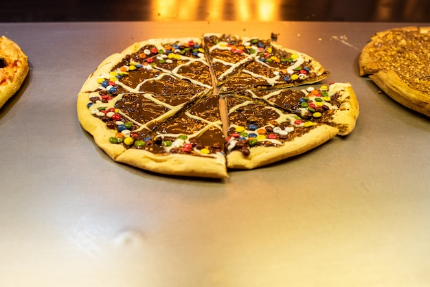 Chocolate pizzas and sweets in a restaurant. Premium Photo