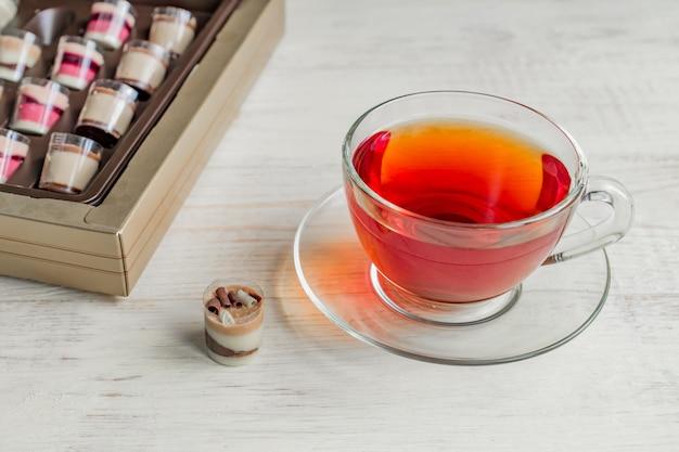Шоколадные конфеты пралине и чашка черного чая на белом фоне деревянные Premium Фотографии
