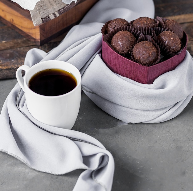 Chocolate pralines and a white cup of coffee Free Photo