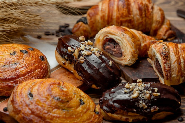 Cornetto di pasta sfoglia al cioccolato, eclair al cioccolato e rotolo di uva passa dolce Foto Gratuite