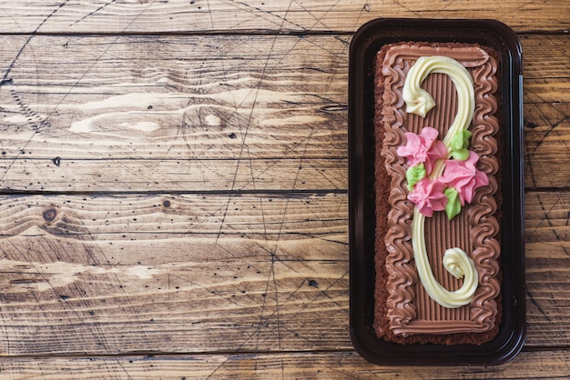 Chocolate rectangular cake decorated with cream roses Premium Photo