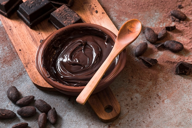 Chocolate sauce with chocolate bar pieces and cocoa beans Premium Photo