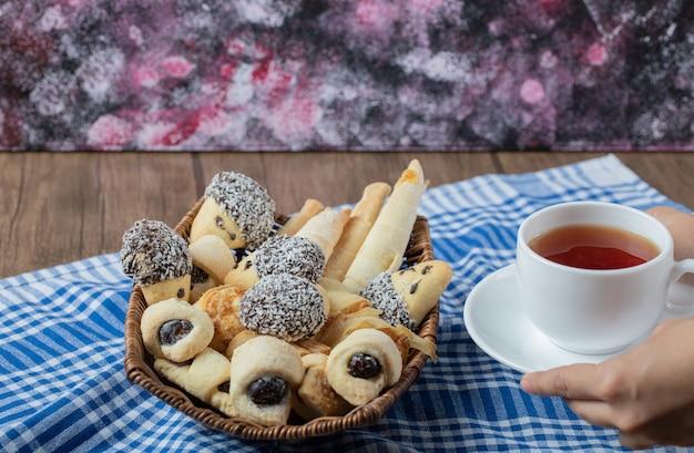 アールグレイティーのカップと木製のバスケットにチョコレートゴマクッキー。 無料写真