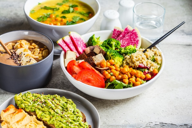 Chocolate smoothie bowl, buddha bowl with tofu, chickpeas and quinoa, lentil soup and toasts Premium Photo