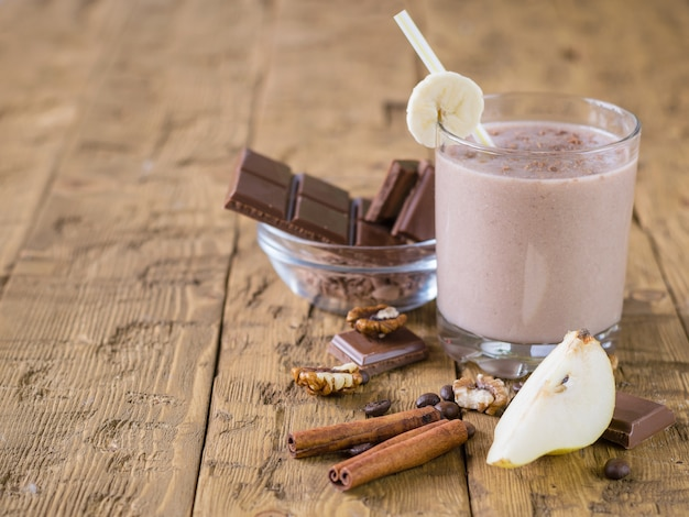 Chocolate smoothie with banana and pear on vintage rustic table. Premium Photo