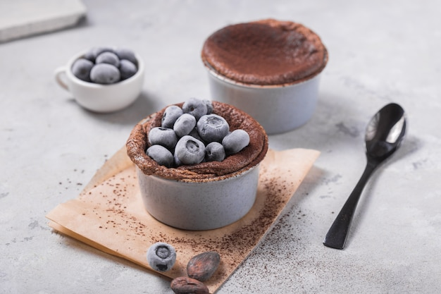 Chocolate souffle with frozen blueberry. french traditional dessert. Premium Photo
