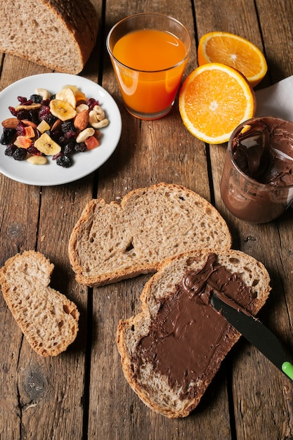 Chocolate spread on bread slice with orange juice Free Photo