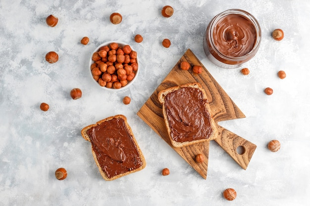 Chocolate spread or nougat cream with hazelnuts in glass jar on concrete ,  copyspace Free Photo