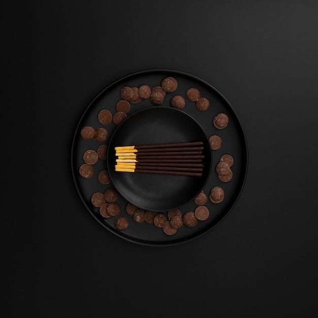 Chocolate sticks plate on a dark background Free Photo