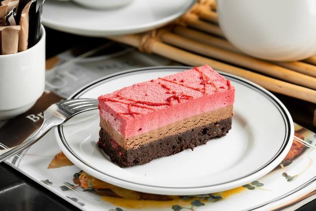 Chocolate and strawberry cheesecake plate garnished with strawberry syrup Free Photo