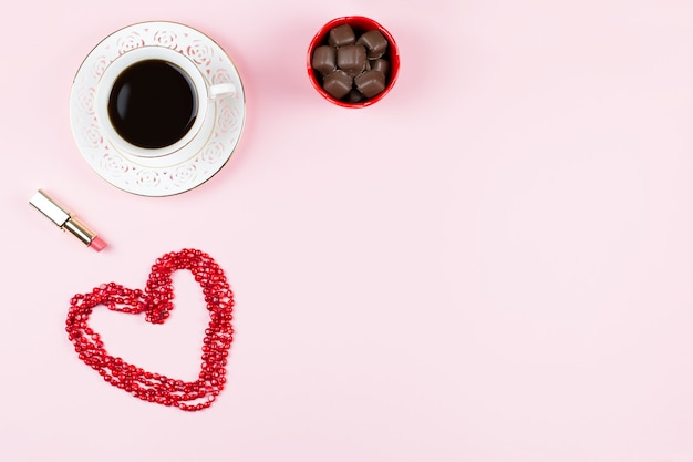 Chocolate sweets, hot drink, lipstick. feminine background in pink, red and white colors. flat lay, copy space. Premium Photo