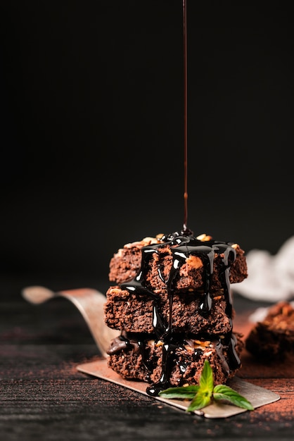 Chocolate syrup poured over tower of chocolate nut brownies on tray Free Photo