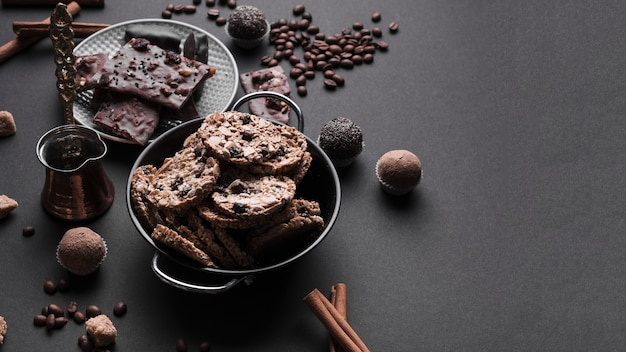 Chocolate truffles and healthy oats cookies in utensil on black backdrop Free Photo