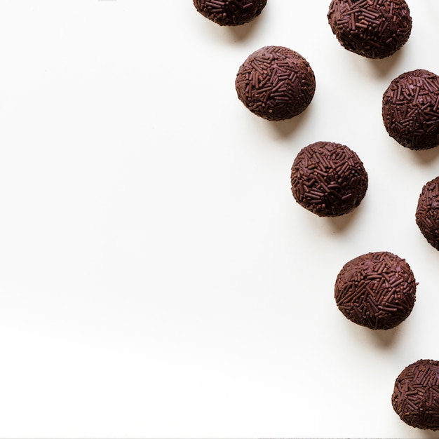 Chocolate truffles in a row on white background Free Photo