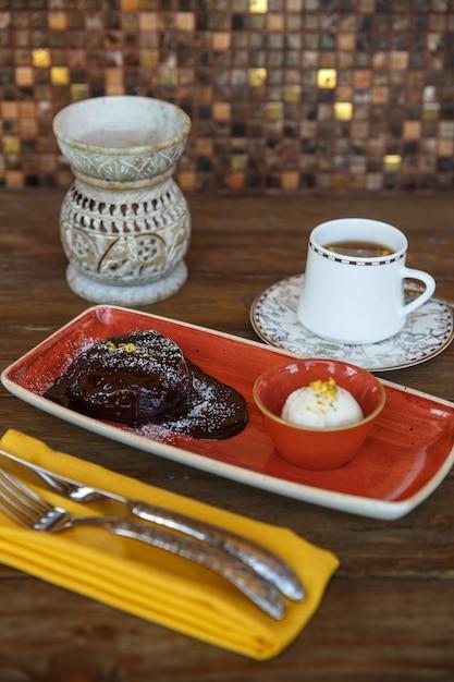 Chocolate volcano served with vanilla ice cream and tea Free Photo