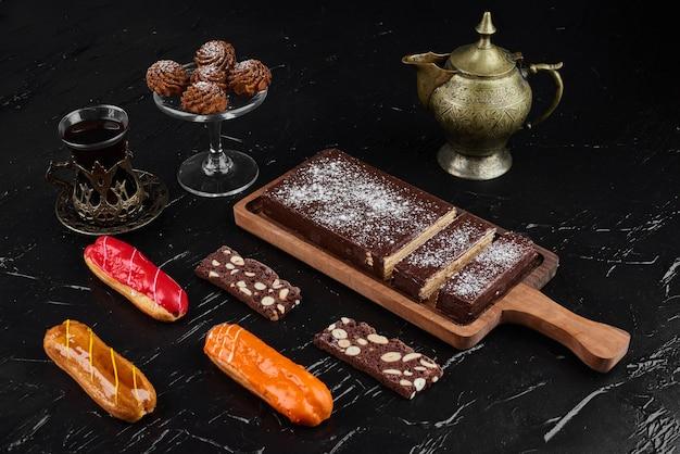 クッキーとエクレアが付いている木製の大皿にチョコレートワッフル。 無料写真