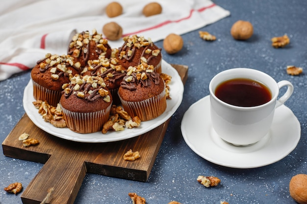 Chocolate-walnut muffins with coffee cup with walnuts on dark surface Free Photo