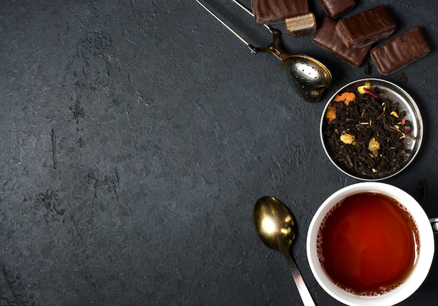 Chocolates and black tea with herbs. metal tea strainer, spoon. Premium Photo