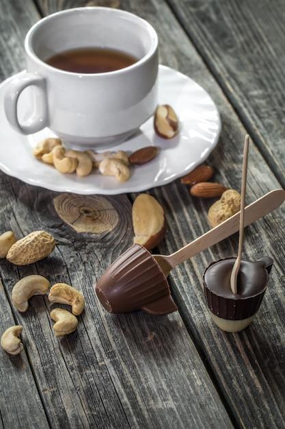 木製の背景にお茶とナッツとチョコレート 無料写真