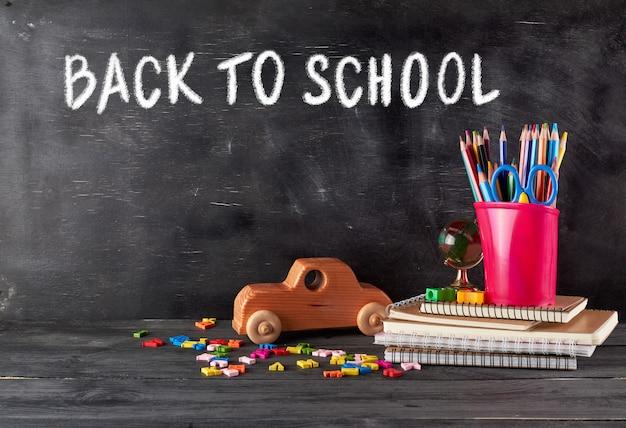 Chool supplies: notebook, pencils, scissors and a wooden retro toy car Premium Photo
