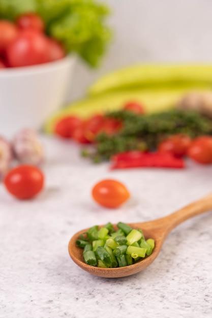 Нарезанный зеленый лук на деревянной ложкой с перцем и помидорами на белом цементном полу. Бесплатные Фотографии