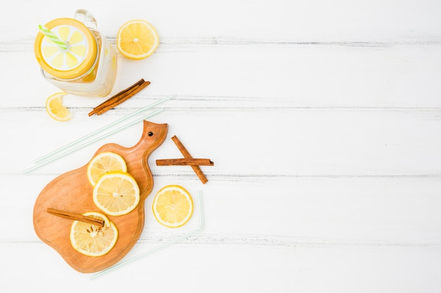 Chopping board with lemons near cinnamon and straws with glass Free Photo