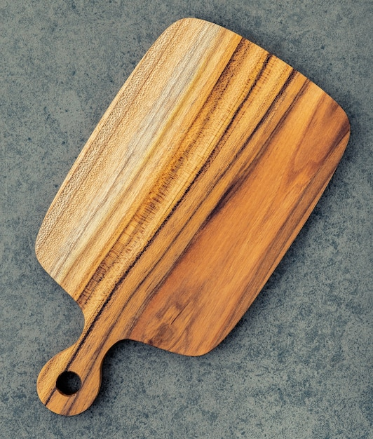 Chopping teak wood cutting board on dark stone background. Premium Photo