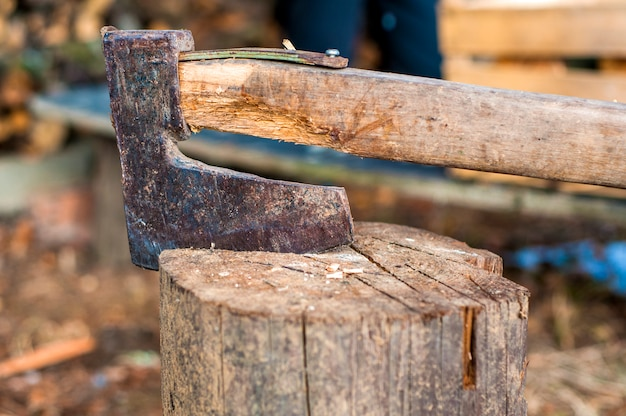 Chopping wood with ax. ax stuck in a log of wood Free Photo