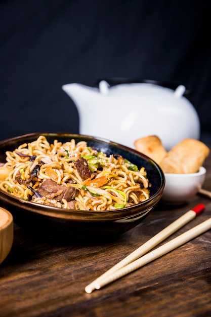 Chopsticks and bowl of delicious noodles with beef on wooden desk Free Photo