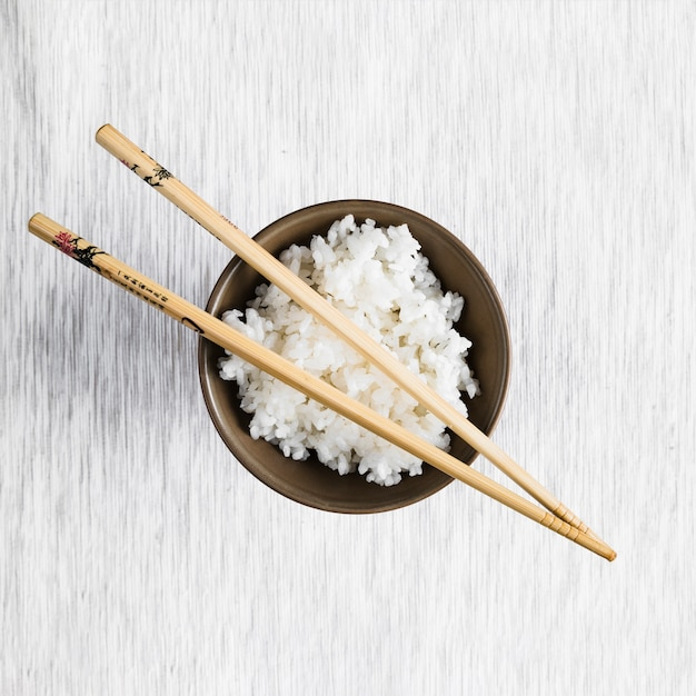 Chopsticks on bowl with rice Free Photo