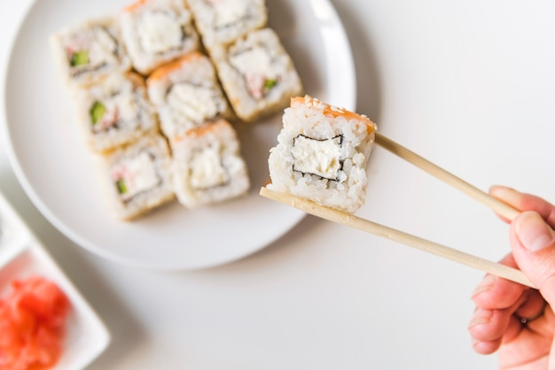 Chopsticks holding a sushi roll Free Photo
