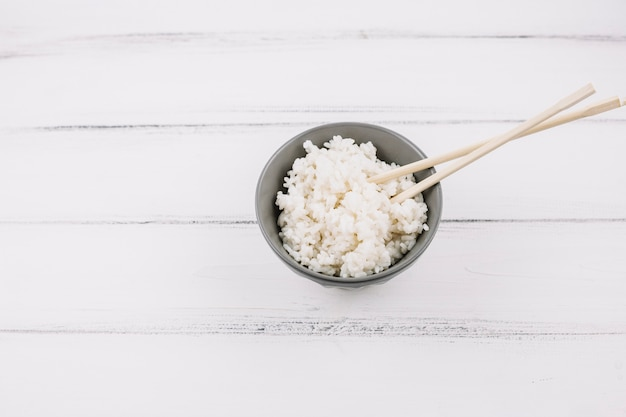 Chopsticks in bowl with rice Free Photo