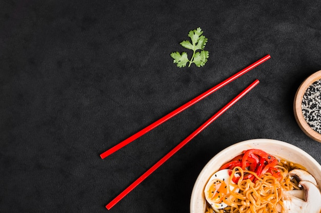 Chopsticks; parsley leaf and bowl of noodles with egg; mushroom and bell peppers Free Photo