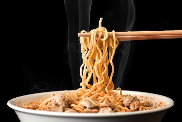 Chopsticks pick up tasty noodles with smoke on dark background. ramen in white bowl. Premium Photo