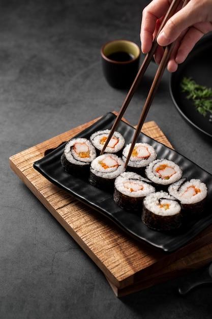 Chopsticks picking up maki sushi rolls Free Photo