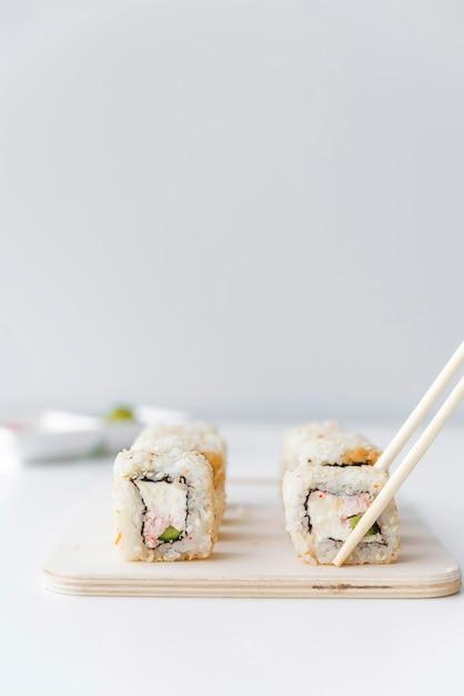 Chopsticks picking up sushi roll Free Photo