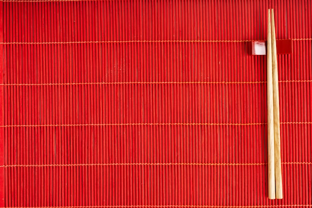 Chopsticks on the red bamboo mat over the gray stone background with copy space. mockup for the menu. Premium Photo