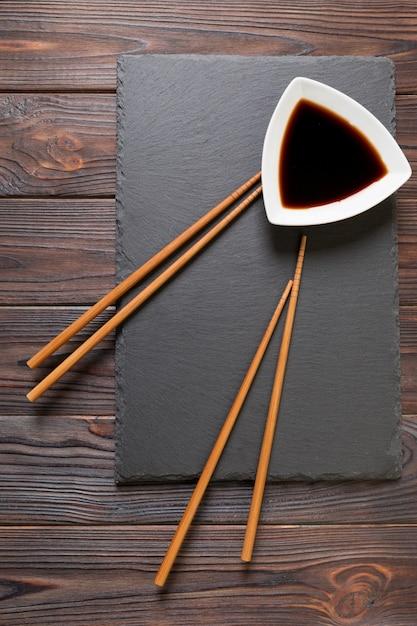 Chopsticks and soy sauce on black stone plate Premium Photo