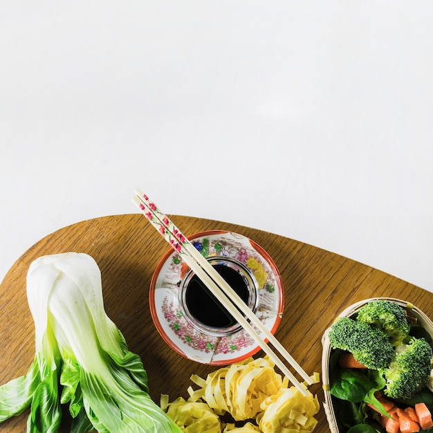 Chopsticks on soy sauce near vegetables | Free Photo