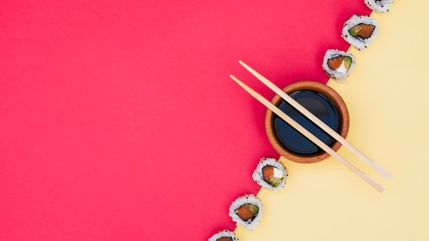 Chopsticks over the soya sauce bowl with sushi on yellow and red dual backdrop Free Photo