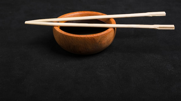 Chopsticks over the soya sauce wooden bowl on black backdrop Free Photo