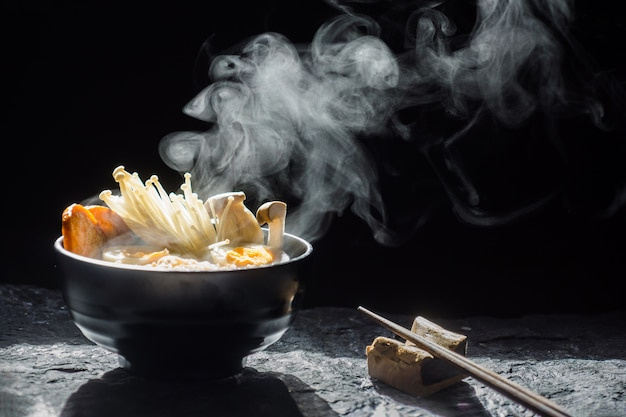 Premium Photo   Chopsticks to tasty noodles with steam and smoke in bowl on  dark background