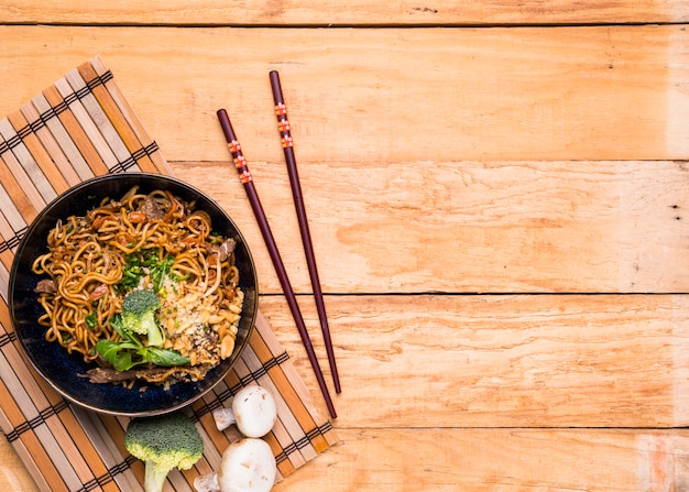 Chopsticks and thai udon noodles with beef and broccoli on wooden table Premium Photo