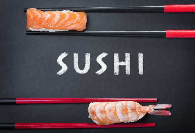 Chopsticks and two sushi and an inscription Premium Photo