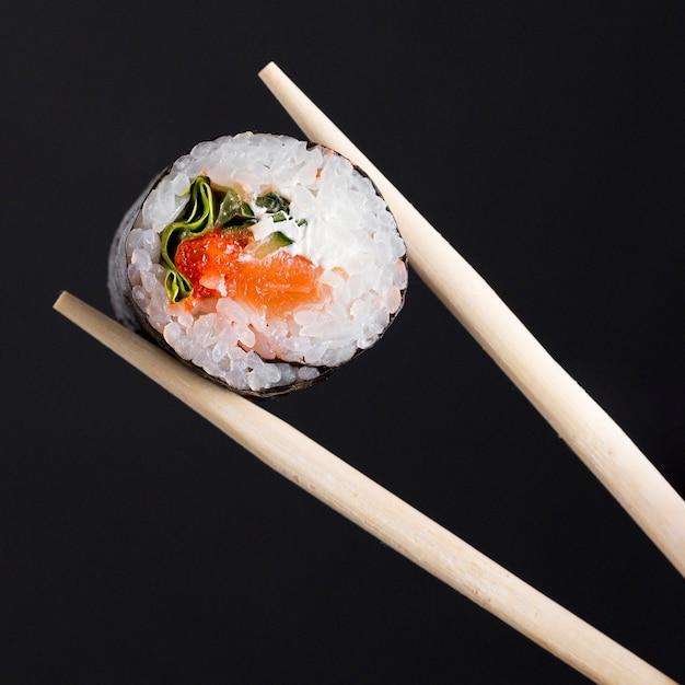 Chopsticks with sushi roll Premium Photo