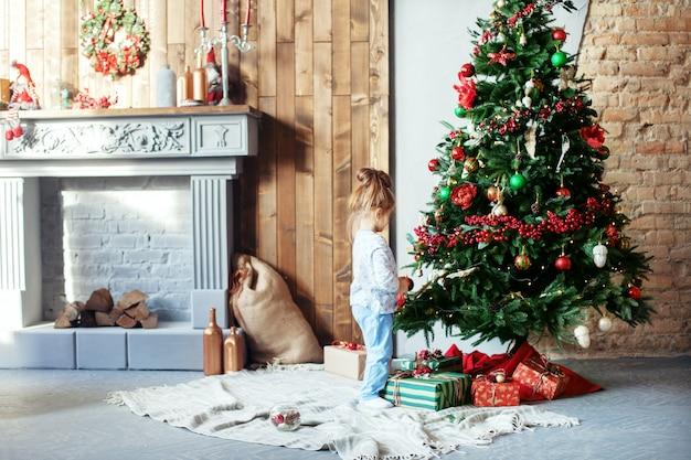 小さな娘がクリスマスツリーを飾る。 chrの概念 Premium写真